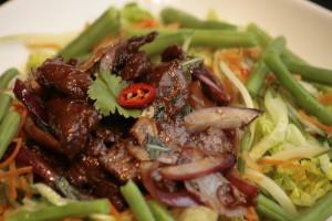 I3 Yam Nua Maaltijdsalade van ossehaas, Thaise basilicum, uien, baby gem, komkommer, sperziebonen, cherrytomaten, limoen, vissaus, peper en koriander.