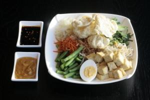 I4 Gado Gado Witte kool, taugé, komkommer, sperziebonen, waterspinazie, tofu, ei, gebakken uien, emping Melindjo, pittige ketjapsaus, pindasaus en witte rijst.
