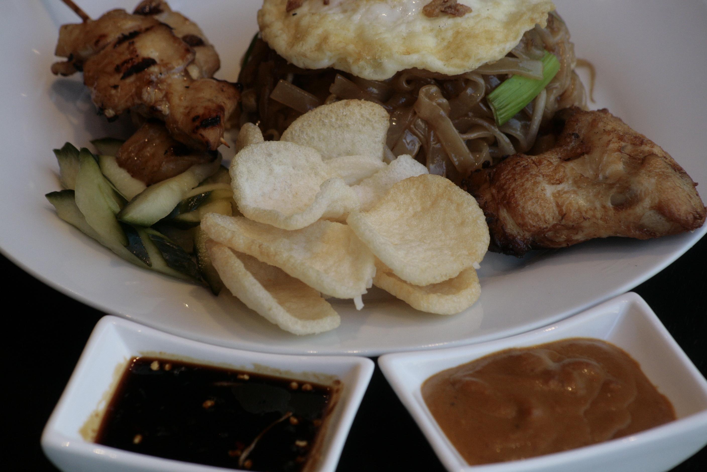 K6 Djawa Plate (Bami Goreng) Javaans gebakken bami met Saté Ajam (2), Mama's gebakken kip, spiegelei, Acar Ketimun en Kerupuk Udang.